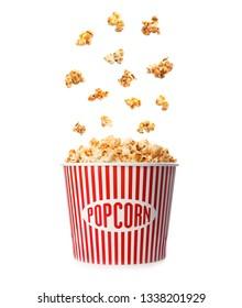 Delicious caramel popcorn falling into carton bucket on white background