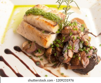 Delicious caribbean dish with grilled grouper fish fillets with sautéed mushrooms and greens