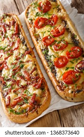 Delicious casserole sandwich with bacon, mushrooms, tomatoes and mozzarella cheese close-up on the table. vertical