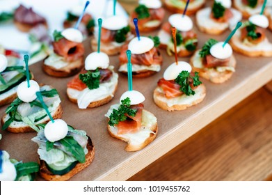 Delicious catering banquet buffet table decorated in rustic style in the garden. Different snacks, sandwiches with salmon, fish, greenery, eggs, mozzarella and pesto sauce. Outdoor, closeup.