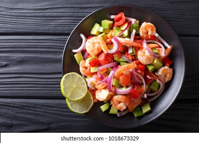 Delicious ceviche of shrimp with vegetables, spices and lime close up on a plate on the table. horizontal top view from above