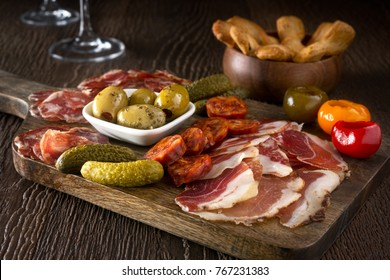 A delicious charcuterie assortment of meat, olives, gherkins, and pickled peppers with breadsticks on a wooden background.