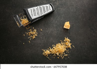 Delicious cheese and grater on dark background