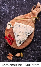 Delicious cheese on a board, on a dark background. Blue Cheese.