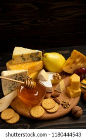 Delicious cheese on the table. Various types of cheese on a rustic wooden table. Assortment of cheeses with nuts, fruits and honey. Free space for text.