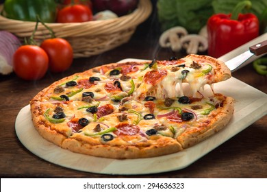 Delicious cheese stringy slice lifted of full supreme pizza baked fresh out of the oven next to ingredients