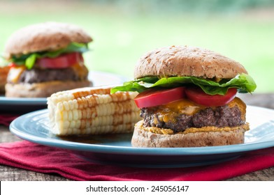 Delicious cheeseburger with corn on the cob