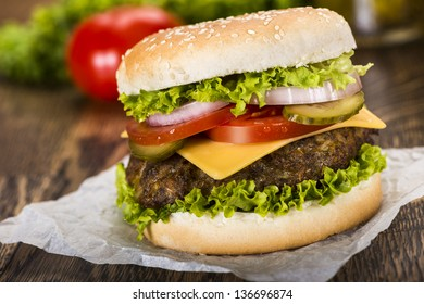 Delicious cheeseburger with a juicy beef, cheese, fresh lettuce, onion, pickle and tomato on a sesame seed bun photographed on a baking paper on a wooden table