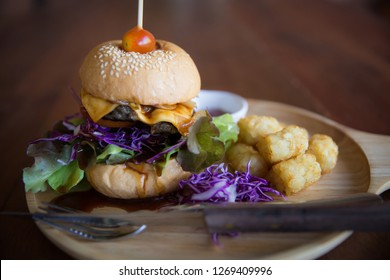 A delicious cheeseburger platter with a side of tator tots on a wooden platter