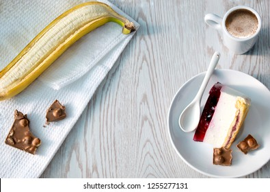 Delicious cheesecake, banana, pieces of chokolates and cup of cofee on wooden background. Flat lay