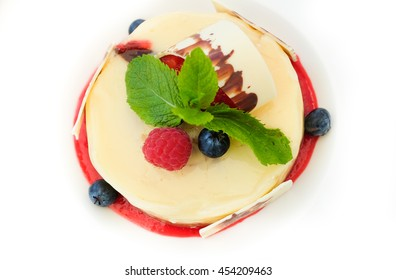 Delicious cheesecake with berries and mint on the white plate. Top view