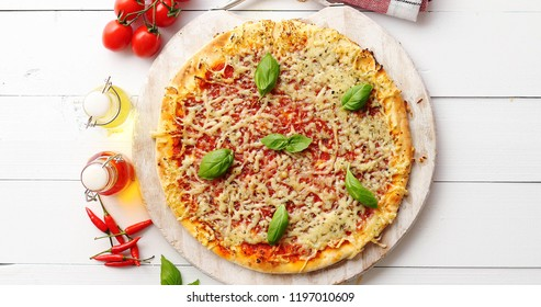 Delicious cheesy italian pizza served on white rustic wooden table with ingredients around. Shot from above.