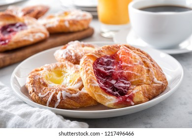 Delicious cherry and lemon mini danishes on a marble table top with black coffee and orange juice.