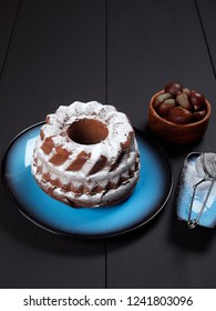 Delicious chestnut bundt cake using sweetened chestnut purée and chocolate chips, dusted with sugar, set on a blue plate, on a dark brown background