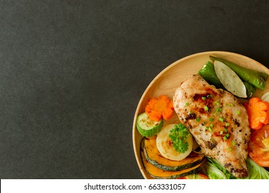 Delicious chicken breast barbecue or chicken steak for lunch or dinner on wood plate put on granite table in top view flat lay, copy space. Homemade food concept.