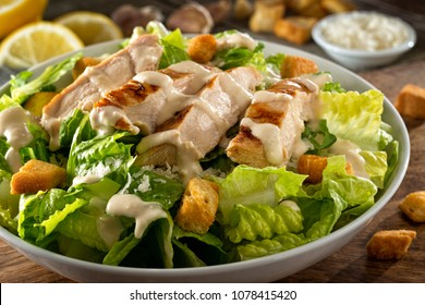 A delicious chicken caesar salad with parmesan cheese, dressing and croutons.