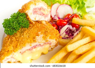Delicious chicken Cordon bleu serve with french fries and salad on white background
