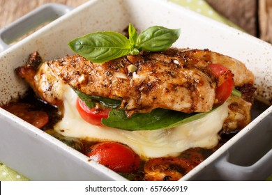 Delicious chicken fillet baked with caprese close-up in a baking dish on a table. horizontal