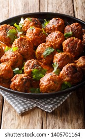 Delicious chicken meatballs in a creamy coconut sauce with curry closeup on a plate on the table. vertical