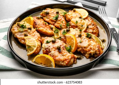 Delicious chicken piccata with sauce and lemon on plate