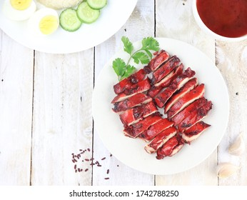 Delicious Chinese Cuisine Ayam Char Siu or Grilled Char Siu Chicken or Char Siew, vibrant red chicken made from angkak or red yeast rice. Served in white plate on wooden table. Selective focus.