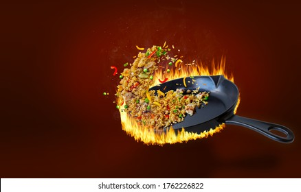Delicious Chinese fried rice being stir fried in hot flaming pan and tossed in midair with chicken, peppers, peas, carrots and onion. Rising steam and seasoning sprinkles with copy space.