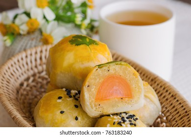 Delicious Chinese pastry or moon cake filled with mung bean paste and salted egg yolk on wood basket served with tea on wood table in side view, close up. Homemade bakery concept.