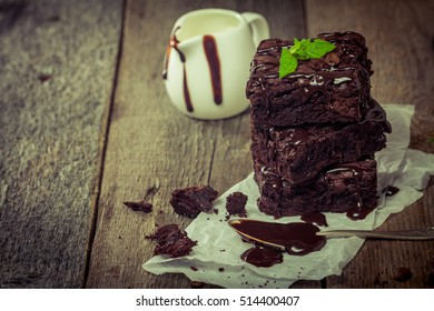 Delicious chocolate brownie with mint on wooden table.