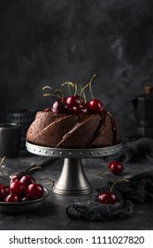 delicious chocolate bundt cake with fresh cherry on dark background, selective focus