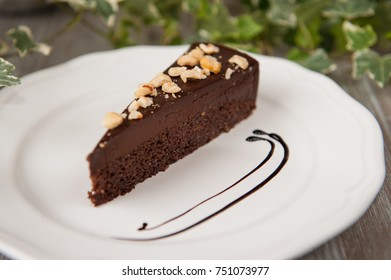 Delicious chocolate cake with almonds on plate on table