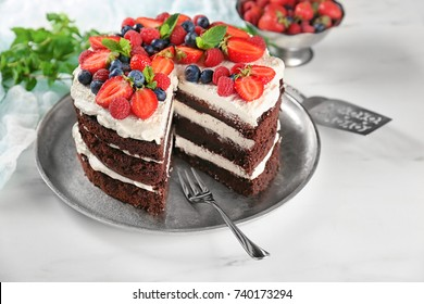 Delicious chocolate cake with berries on table