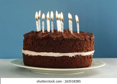 Delicious chocolate cake with candles on table on blue background