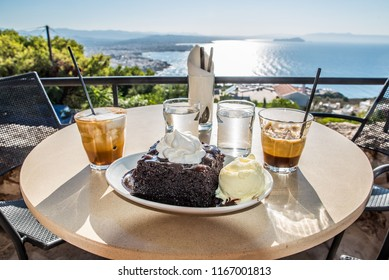 A delicious chocolate cake with cream on top and ice cream on the side with two coffes and two glasses of water around it with balcony view