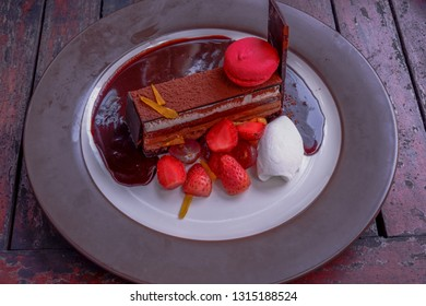 Delicious chocolate cake with fresh strawberries and grapes on a wooden table