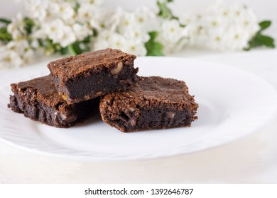 Delicious chocolate cake on a white plate on a white table. Homemade pastries. Traditional American Pie. Copy space