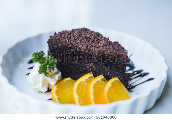 delicious chocolate cake on white plate with citrus, closeup.