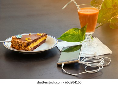 Delicious chocolate cake and smartphone with iced tea glass or orange juice in coffee shop on table blurred background.