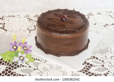 Delicious chocolate cake with a strawberry and decorative flowers on a table