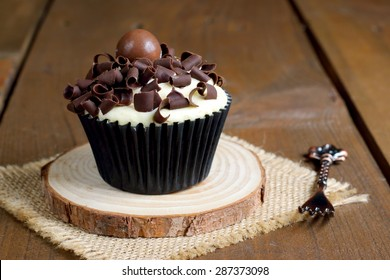 Delicious chocolate cupcake on a wooden brown rustic table