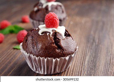 Delicious chocolate cupcakes with berries on table close up