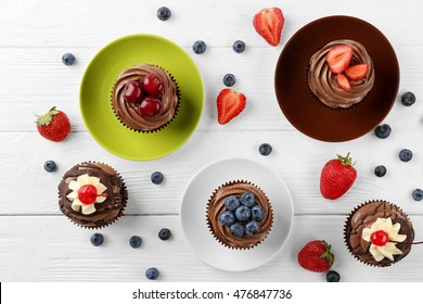 Delicious chocolate cupcakes on colorful plates, top view
