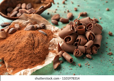 Delicious chocolate curls with cocoa powder on color background