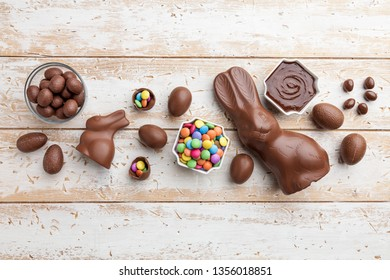Delicious chocolate Easter bunny, eggs and sweets on rustic background