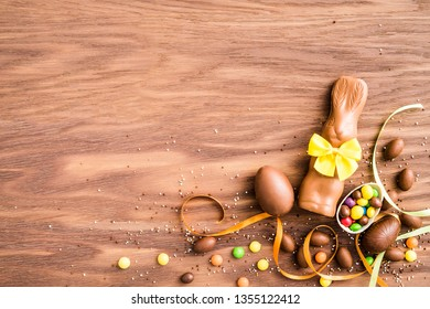 Delicious chocolate easter eggs ,bunny, colorful sweets and candies on a wooden background.