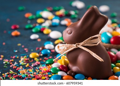 Delicious chocolate easter eggs ,bunny and sweets on dark blue background,easter concept background