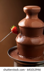 Delicious chocolate fountain fondue with a ripe red strawberry on a fork dripping the sauce after being dipped and copy space behind