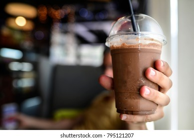 A delicious chocolate frappe in plastic cup in man,woman's hand with blur background in coffee shop early morning.