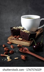delicious chocolate fudge cake wiht almond slide and on wooden with almond , cherry on a dark background. Space for text. Party, birthday, festive concept.