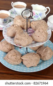 Delicious chocolate meringues on pretty cake stand with elegant china tea set