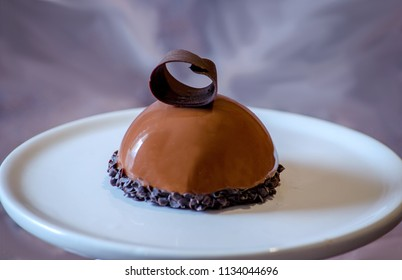 delicious chocolate mouse cake with a chocolate curl, on a ceramic plate